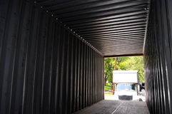 Moving container. Looking from the inside of a shipping container towards the open doors, with a moving truck (altered features, not a recognizable model) Stock Images