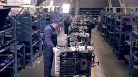 Moving Conveyer with engines. Worker making truck engines. stock video