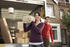 Moving Couple Carrying Rolled Carpet. Portrait of happy young couple carrying rolled carpet by moving van Stock Images