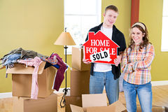 Moving: Couple Holding Up Home Sold Sign Royalty Free Stock Images