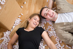 Moving: Couple Laying On Floor Amid Packing Peanuts Royalty Free Stock Photography