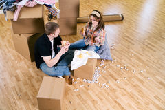Moving: Couple Sits On Floor Having Lunch While Packing Royalty Free Stock Photos