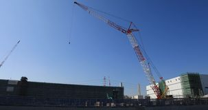 Moving cranes behind the blue sky at the under construction wide shot. Moving cranes behind the blue sky at the under construction. Niiza-shi Saitama Japan - 01 stock video footage