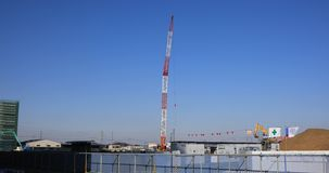 Moving cranes behind the blue sky at the under construction wide shot. Moving cranes behind the blue sky at the under construction. Niiza-shi Saitama Japan - 01 stock video