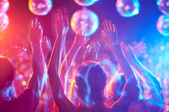 Moving in dance. Crowd of young people dancing in night club Royalty Free Stock Photography