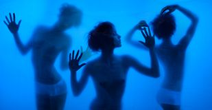 Moving and dancing silhouettes of women. Behind the washing curtains and blue background Royalty Free Stock Photos