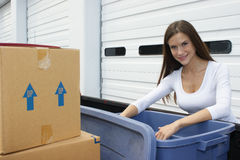 Moving Day Woman Fills Rubber Storage Bin. A Handsome Woman unloads goods to the storage locker Royalty Free Stock Photography