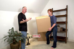 Moving Day. Woman carrying heavy boxes with man gesturing in room of their new home Royalty Free Stock Photo