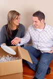 Moving Day. Young Couple Sat On The Floor Unpacking Boxes In Their New Home Stock Image