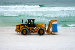 Moving day on the beach. Heavy equipment moving a port a potty down the beach Stock Photo