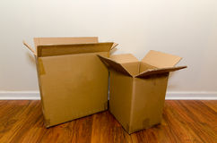 Moving Day Boxes. Moving day with empty cardboard boxes on hardwood floor Stock Photos