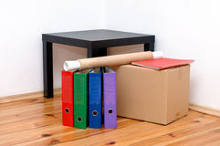 Moving day - cardboard boxes in room. Moving day - cardboard boxes with table and files in room Royalty Free Stock Photos