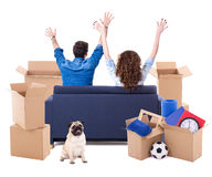 Moving day concept - back view of cheerful couple sitting on sof Stock Photography