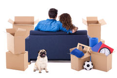 Moving day concept - back view of couple sitting on sofa with br Royalty Free Stock Images