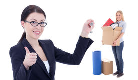 Moving day concept - business woman with metal key and girl with Royalty Free Stock Photos