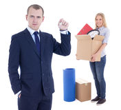 Moving day concept - businessman real estate agent giving key to Stock Photography
