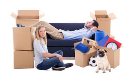 Moving day concept - tired couple and cardboard boxes with stuff royalty free stock photos