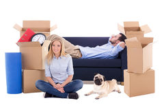 Moving day concept - tired young couple with brown cardboard box Royalty Free Stock Images
