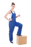 Moving day concept - young attractive woman in blue coveralls wi Stock Photo