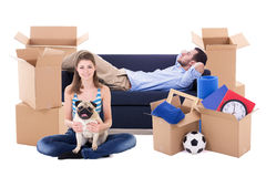 Moving day concept - young couple with brown cardboard boxes wit Stock Images