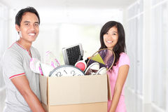 Moving day. couple with their stuff inside the cardboard box Royalty Free Stock Image