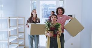Moving day for a couple young married a friend enter into the house she was impressed of the house design while holding. Two flowers , couple and friend enter stock video footage