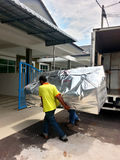 Moving Day. Movers unloading a moving van, passing a cardboard box Stock Photo