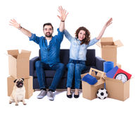 Moving day and new home concept - cheerful couple sitting on sof Royalty Free Stock Photography