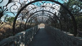 Moving through decorative tunnel arch made of metal in designed tracery stock video