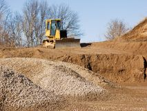Moving Dirt. Bulldozer set on top of hills of dirt Royalty Free Stock Photos