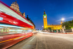 Moving Double Decker Bus under Houses of Parliament and Big Ben. Royalty Free Stock Photo