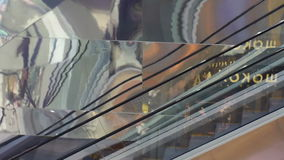 Moving escalator in modern building closeup. Wall with reflections stock video footage