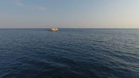 Approaching an Islet. Moving fast over the sea surface while approaching an islet stock footage