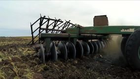 Moving plow on the field. Slow motion. Moving on the field and plowing the land trailer plow. Slow motion stock video