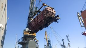 Moving freight railway car in the port by a port crane. Cargo li Royalty Free Stock Images