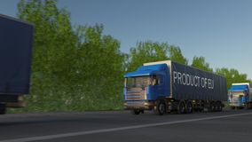 Moving freight semi trucks with PRODUCT OF EU caption on the trailer. Road cargo transportation. Seamless loop 4K clip stock video footage