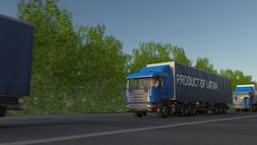 Moving freight semi trucks with PRODUCT OF LATVIA caption on the trailer. Road cargo transportation. Seamless loop 4K clip stock footage