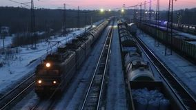Moving freight train on railway at winter evening. Moving long freight train on railway at winter evening stock video