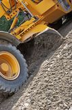 Moving gravel. Industrial machine moving gravel on a new road royalty free stock images