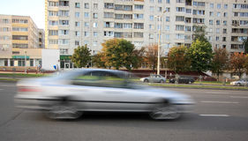 Moving gray car with motion blur effect. Movement of a blurry gray car down the street in the daytime stock photography