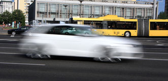 Moving gray car with motion blur effect. Movement of a white blurry car on the street in the daytime stock photos