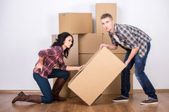 Moving home. Back injury from carrying heavy box while moving to new home Stock Photography