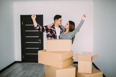 Smiling couple with raisen hands in new home after moving royalty free stock photos