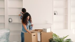 Moving home couple unpacking cozy atmosphere. Moving home. Happy young couple unpacking boxes with decorative stuff, creating cozy atmosphere stock video footage