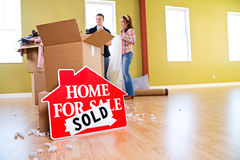 Moving: Home For Sale Sign Sits In Front Of Packing Supplies Stock Photo