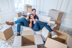 Moving home and repair of a new life. Couple in love pulls thing Royalty Free Stock Image