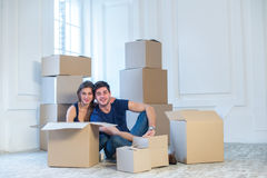 Moving home and repair of a new life. Couple in love pulls thing Stock Photography
