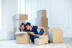 Moving home and repair of a new life. Couple in love pulls thing Royalty Free Stock Images