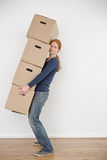 Moving Home - Woman Carrying Boxes. A young woman carrying a large stack of moving boxes into an empty room Stock Images