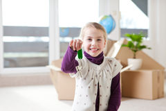 Moving house. A little girl showing the key for the new house in background cardboard boxes,focus on the keys Royalty Free Stock Photo